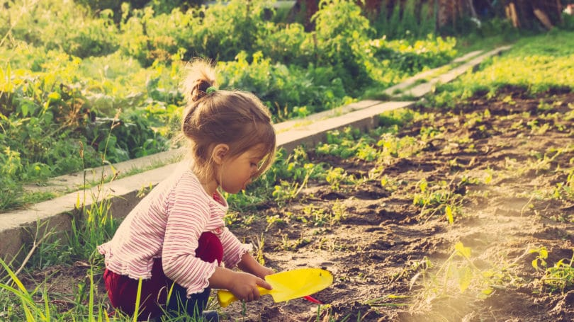 Little Girl Outside Planting Learning Garden