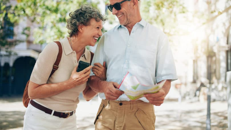 Retired Couple Walking Around Town Smiling Laughing