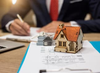 Businessman Signs Contract Behind Home Architectural Model
