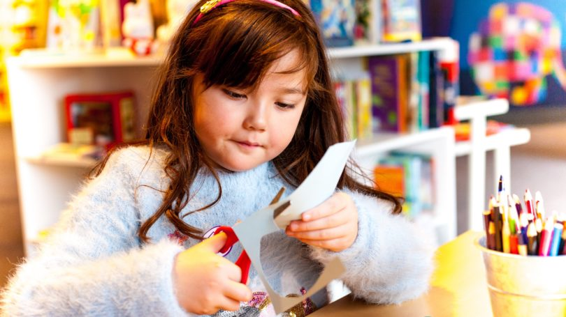 Little Girl Crafting Cutting At Library