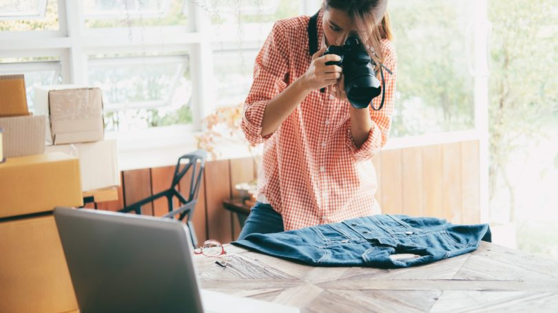 Woman Taking Photo Of Denim Jacket To Sell Online Own Business