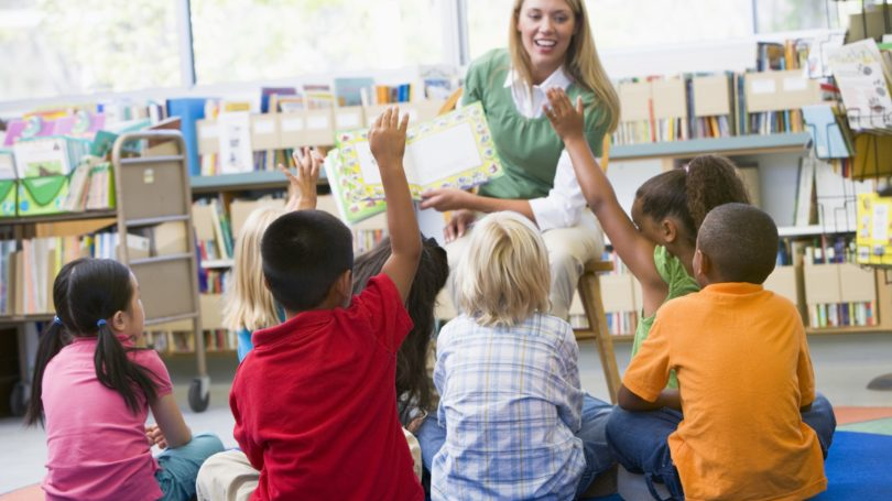 Woman Volunteering At Library Reading For Kids