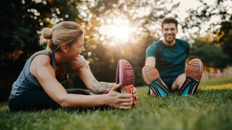 Couple Exercising Together Outdoors Stretching Running