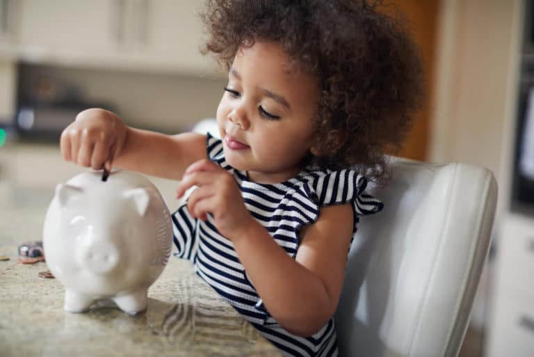 Child Putting Coins Into Piggy Bank