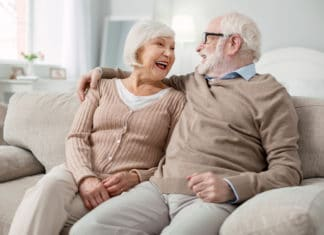 Elderly Couple Sitting On Couch Living Room Laughing