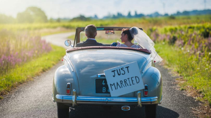 Just Married Couple Driving To Honeymoon Vintage Car Country