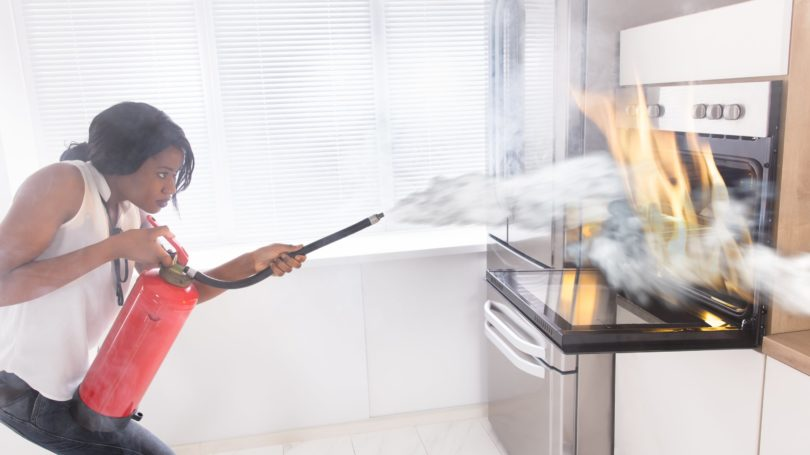 Woman Extinguishing Fire In Kitchen Oven