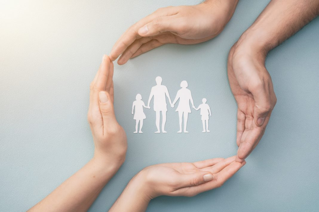 Hands Encircling Cut Out Silhouette Of Family