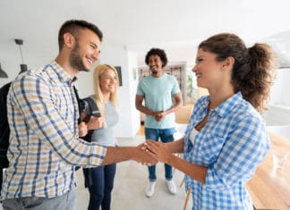 Woman Shaking Mans Hand Apartment