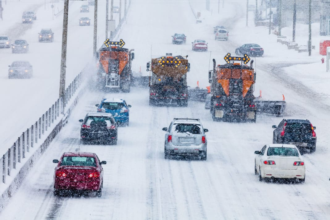 Cars Driving On Big Road Behind Snow Plow Trucks