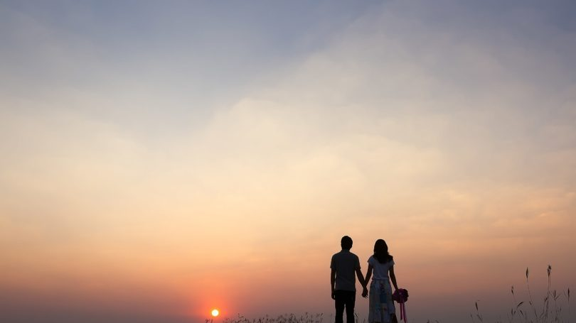 Couple Holding Hands Watching Sunrise Outdoors