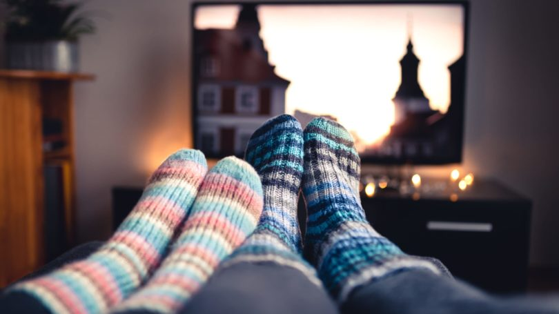 Couple Wearing Socks Sitting On Couch Watching Movie