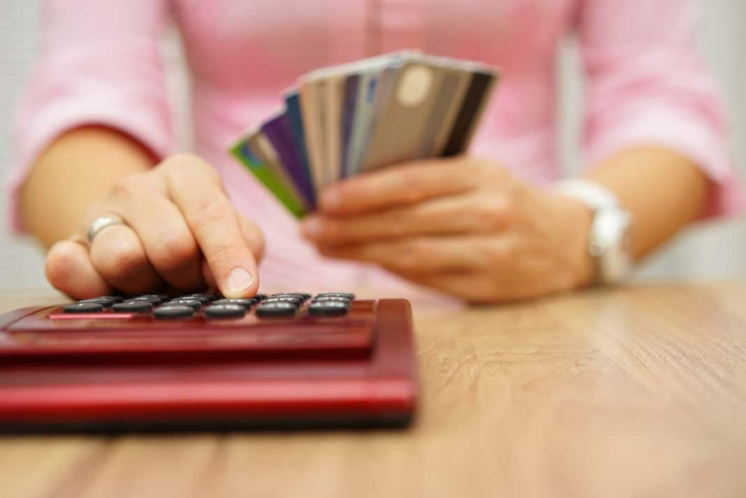 Woman Calculating Bills Holding Stacks Of Credit Cards