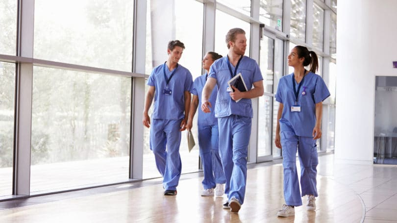 Healthcare Workers In Scrubs Walking In Hospital
