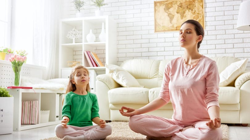 Mom Daughter Meditating In Livingroom