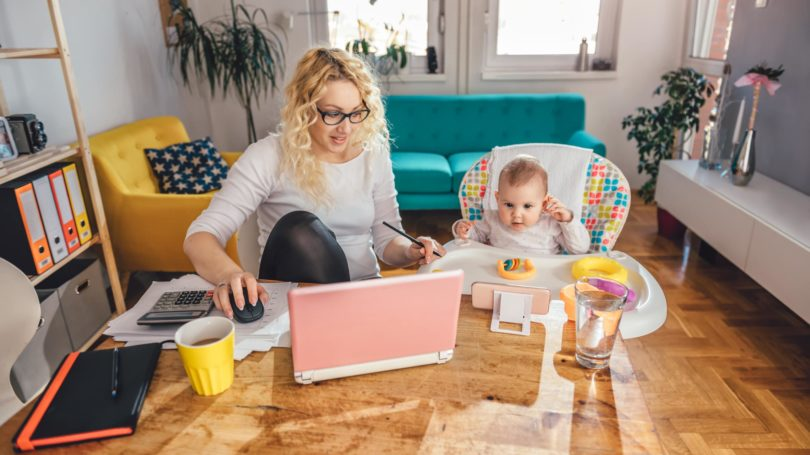 Mom Wearing Glasses Working With Baby Dining Table