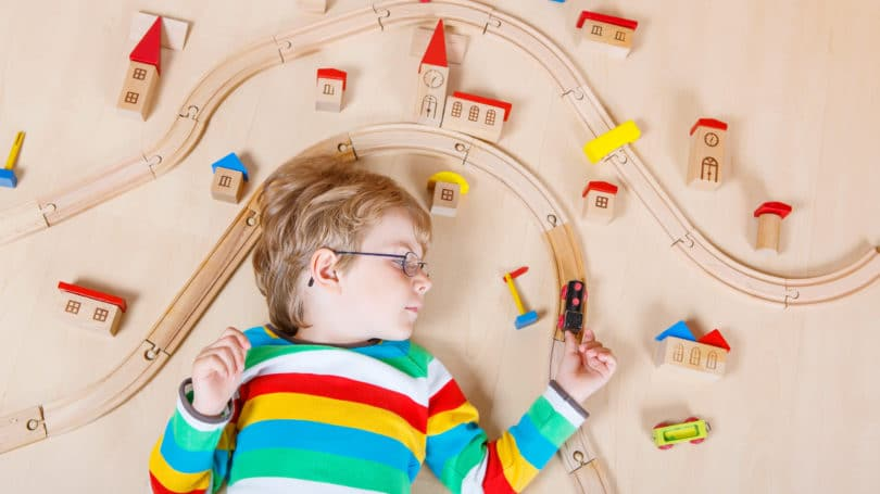 Toddler Boy Wooden Train Set Playing Indoors