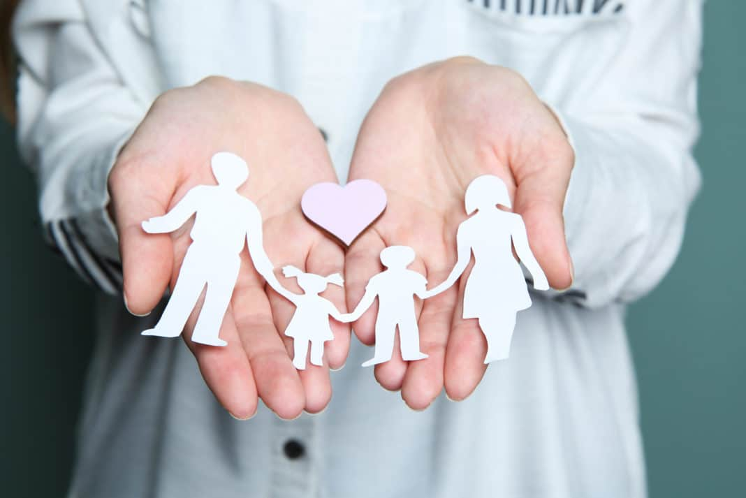 Woman Holding Paper Cut Out Of Family With Pink Heart