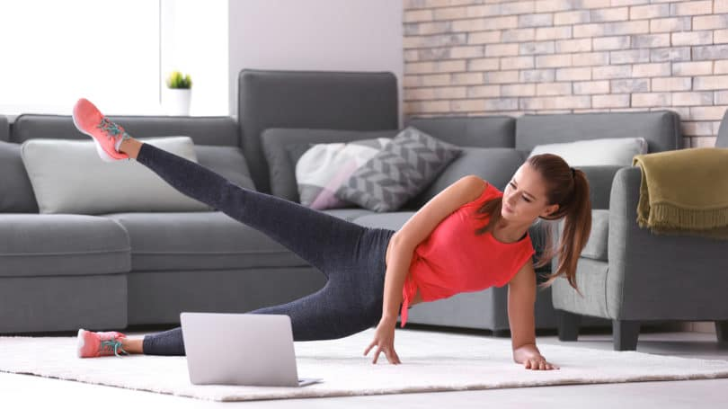 Young Woman Streaming Workout Video Pilates Living Room Laptop
