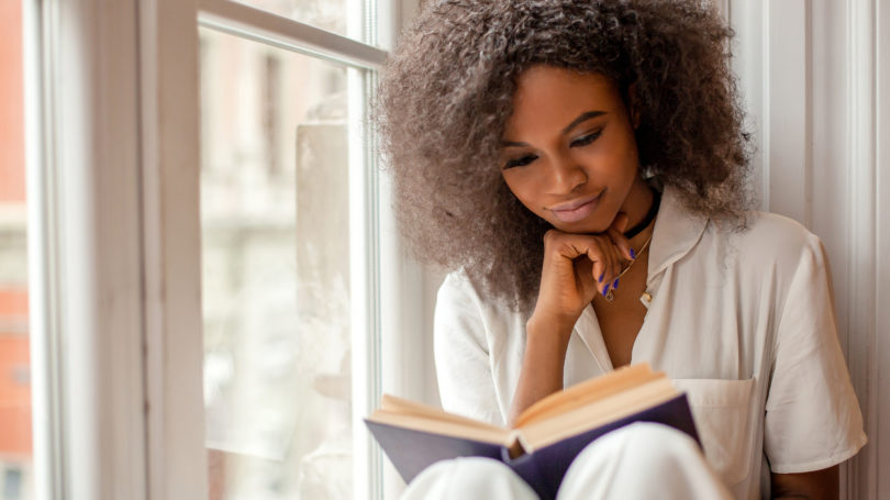 African American Woman Reading A Book By The Window