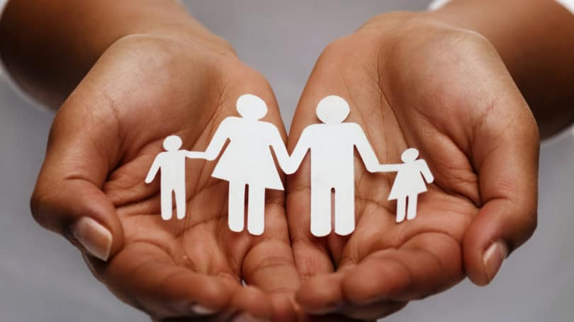 Hands Holding Silhouette Of Family White Cut Out Insurance Policy Concept Covered
