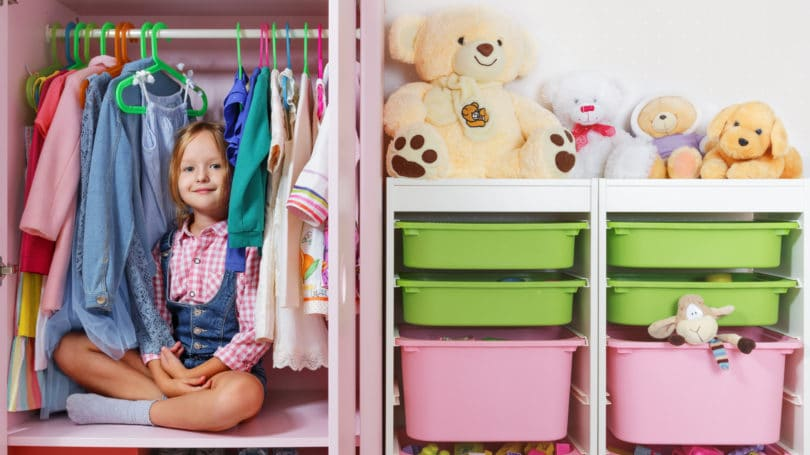 Little Girl Sitting In Wardrobe Closet Clean Organized