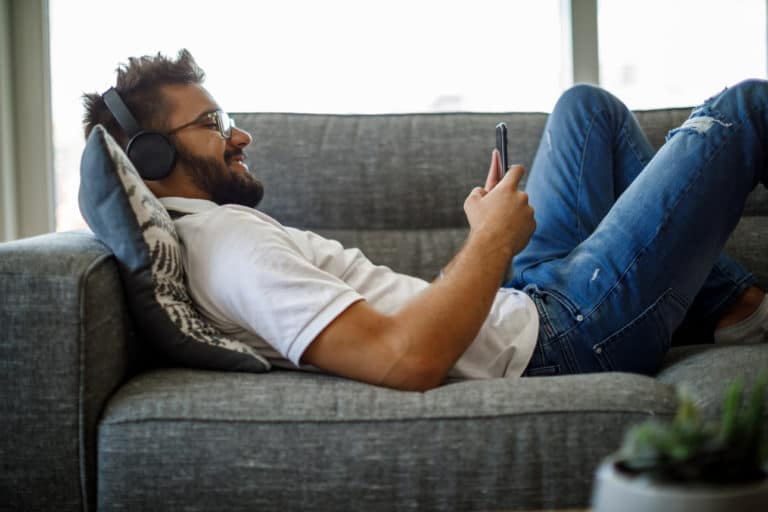 Smiling Young Man With Wireless Headphones Using Smart Phone On Sofa