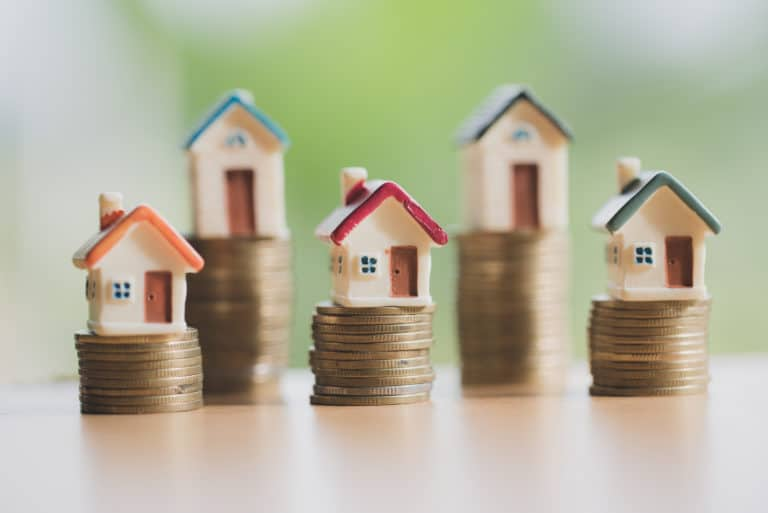 Mini Houses Stacked On Coins Investment Income Revenue