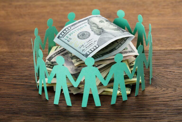 Paper Stick Men Surrounding Money Pile