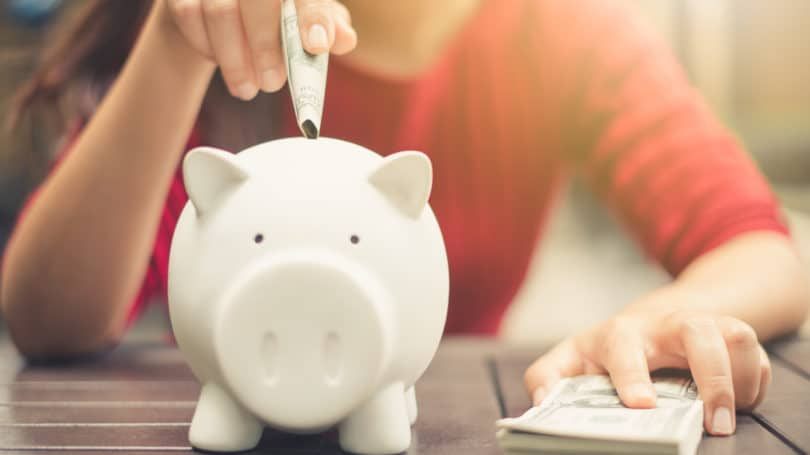 Woman Inserting Cash Into Piggy Bank Savings