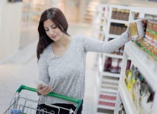 Woman Using Smartphone Holding Canned Good