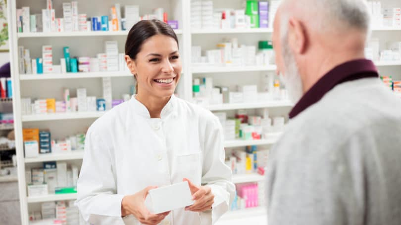 Pharmacist Giving Medicine To Customer Pharmacy