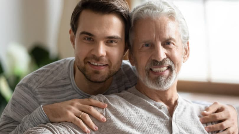 Son And Elderly Father Posing In Living Room
