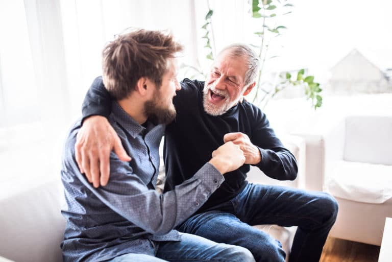 Father Son In Living Room Embraving Sofa