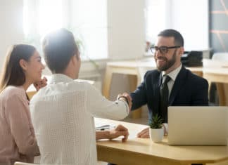 Happy Couple Shaking Hands With Financial Advisor