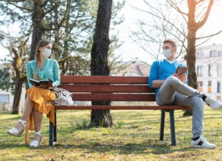 Woman Man Social Distancing At Park Bench Reading