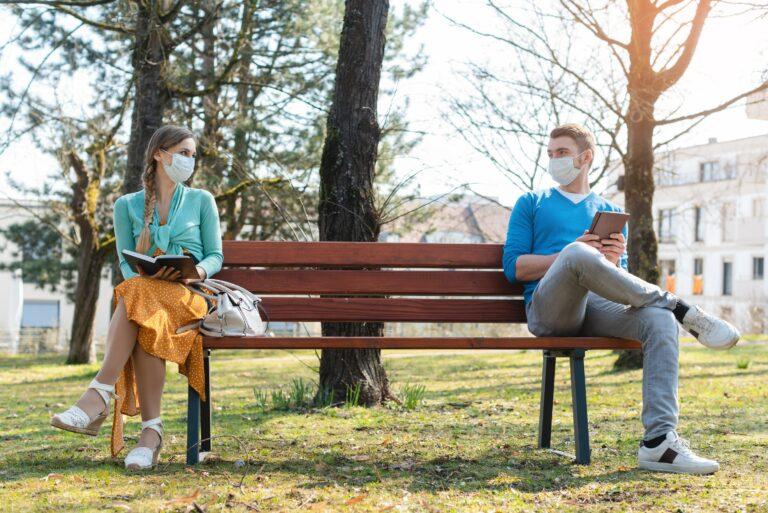 Woman Man Social Distancing At Park Bench Reading