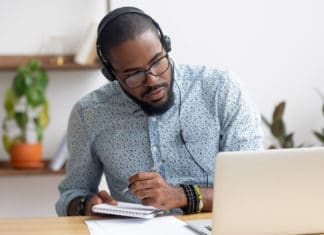 African American Man Studying Online Taking Notes Laptop