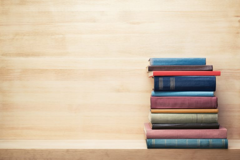 Books On Wooden Shelf Piled Stacked