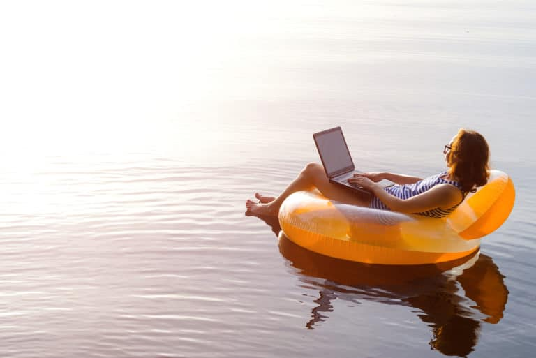 Business Woman Working Remotely On Inflatable Floatie With Laptop In Ocean Lake