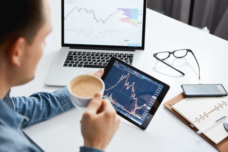 Investor Watching Stock Market On Tablet And Laptop