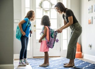 Mother Packing Daughters Backpacks