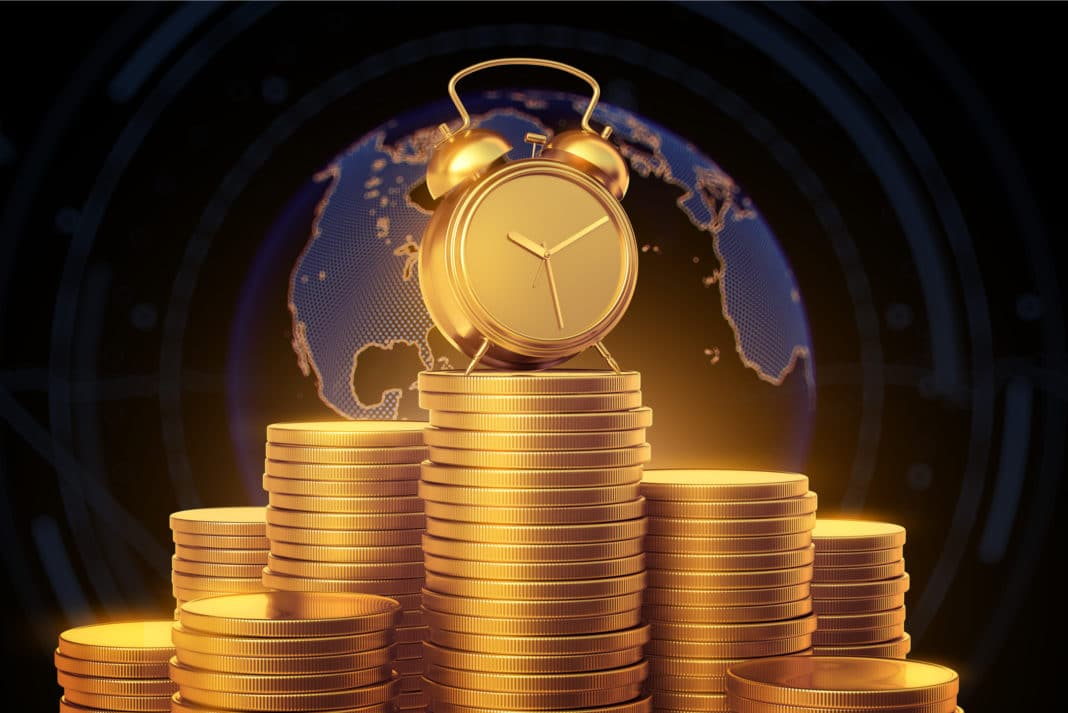 Stack Of Gold Coins With Alarm Clock On Top Globe