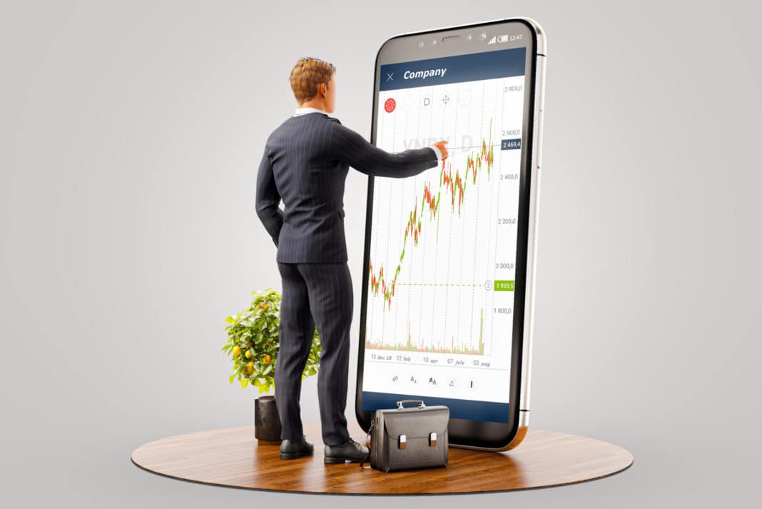 Businessman Standing In Front Of Phone Investing App Stock