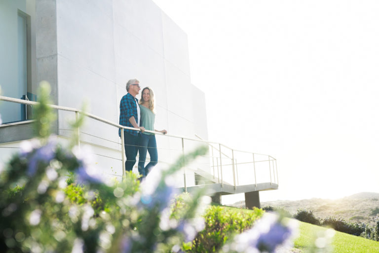 Smiling Couple Standing In Front Of Their Modern Home