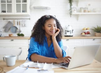 Happy African American Woman Paying Bills Online Laptop Kitchen