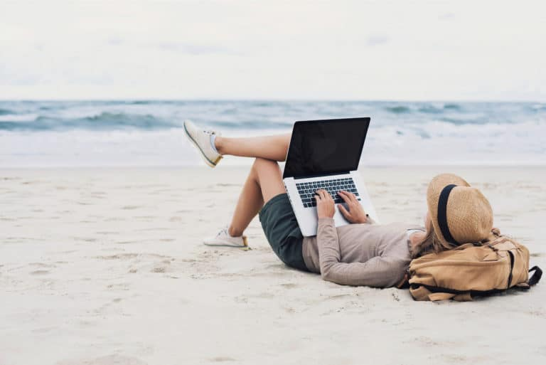 Woman Using Laptop Working From Beach