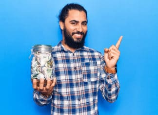 Young Man Holding Jar Of Savings Blue Background