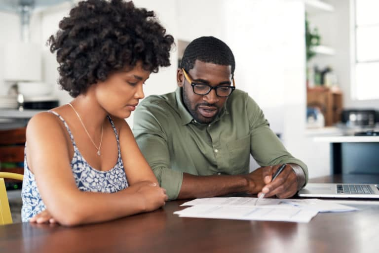 Couple Looking At Papers Discussing Options By Dining Table