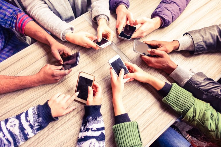 Group Sitting At Table Holding Phones Mobile Friends
